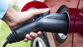 Electric vehicle plugged in stock photography