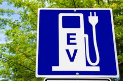 Electric Vehicle Recharging Station Sign with Trees in Background. Blue Sign indicating an Electric Vehicle Recharging Station with Green Trees in Background Royalty Free Stock Photography