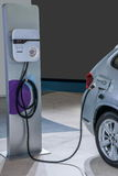 Electric vehicles and electric vehicle charging stations Stock Images