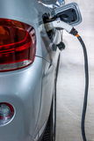 Electric vehicles and electric vehicle charging stations Royalty Free Stock Images