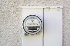 Electric Watt-hour Meter. An Electric Watt-hour Meter on a tan stucco wall Royalty Free Stock Images