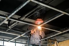 Electric welder in construction site. Busy welder welds  steel frame  in construction site of business building Royalty Free Stock Photography