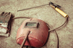 Electric welding machine, electric wire, masks, gloves and tongs, are very old Stock Photography