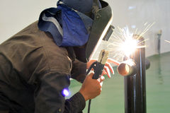 Electric welding at workshop 4. Worker welding the pipe at workshop Royalty Free Stock Photography
