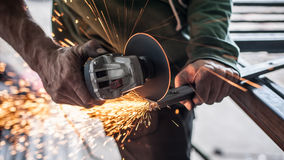 Electric wheel grinding on steel structure in factory Stock Images