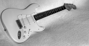 A electric white guitar. Music accompanies us in good times and bad times Stock Images