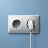 Electric white plug and socket on blue wall Royalty Free Stock Photo