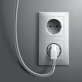 Electric white plug and socket on grey wall Stock Image