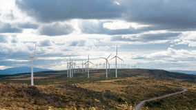 Electric wind mills moved by the wind over cloudy sky background Stock Photos