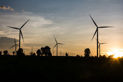Electric wind turbines farm silhouettes on sun background Royalty Free Stock Image