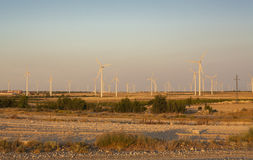Electric wind turbines farm with sunset light on arid landscape. Spain Stock Image