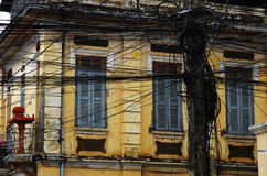 Electric wires in front of a colonial old house. Messy electric wires in Cambodia in front of the windows of a colonial house Stock Photos