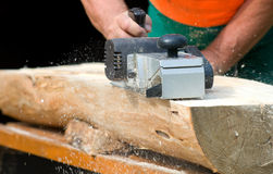 Electric wood planer. Carpenter with electric wood planer at work outdoor Stock Photos