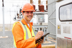Electric worker transformer readings. Portrait of happy young electric worker taking transformer readings Royalty Free Stock Image