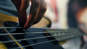 Electrical bass guitar. Strings with fingers on it. Close up stock video