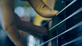 Electrical bass guitar. Strings with fingers on it. Slow motion effect. Close up stock footage