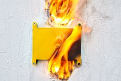 An electrical box that caught on fire. Home electrical fire due to faulty electrical wiring. Inflaming of wall junction box royalty free stock photography