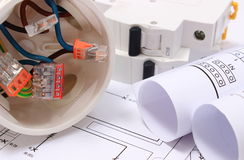 Electrical box, diagrams and electric fuse on construction drawing. Copper wire connections in electrical box, rolls of electrical diagrams and electric fuse on stock photography