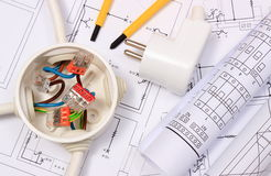 Electrical box, diagrams and electric plug on construction drawing. Copper wire connections in electrical box, rolls of electrical diagrams and electric plug on Stock Image