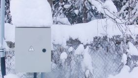 Electrical Box In Winter. Electrical control box with a danger sign, winter landscape in the background stock footage