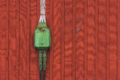 Electrical box on a wooden red background, poweroutlet in green. An old and closed electrical box on a wooden vintage red background outside an old building with Stock Photo