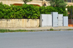 Electrical boxes. A set of electrical boxes on a walkway Stock Photo