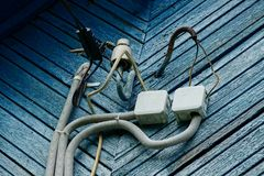 Electrical cable wires and boxes on a blue wooden wall royalty free stock images