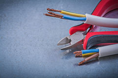 Electrical cables wires nippers on scratched metallic background stock photo