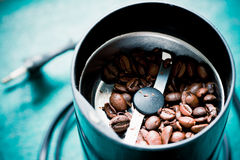 Electrical coffee-mill machine with roasted coffee. Beans on the green tabletop with top cover removed Stock Photos