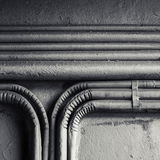 Electrical conduits mounted on old concrete wall. Abstract square industrial background, group of bent vintage electrical conduits mounted on a concrete wall royalty free stock images