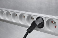 Electrical cord with power strip on grey metal background Royalty Free Stock Photo