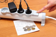 Electrical cords connected to power strip and electricity bill with coins Royalty Free Stock Photo