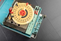 Electrical device for industrial time measurement. An old counter for switching electrical devices. Dark background royalty free stock images