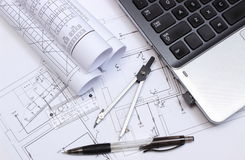 Electrical diagrams, accessories for drawing and laptop. Rolls of electrical diagrams, construction drawings of house, accessories for drawing and laptop stock image