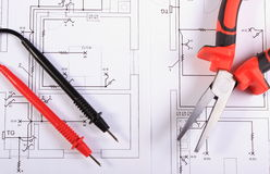 Electrical diagrams, cables of multimeter and metal pliers Royalty Free Stock Photography