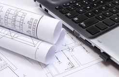 Electrical diagrams, construction drawings and laptop. Rolls of electrical diagrams with construction drawings of house and laptop, drawings and accessories for stock photo