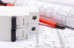 Electrical diagrams, electric fuse and work tools on drawing. Rolls of electrical diagrams, electric fuse and work tools lying on construction drawing of house stock images