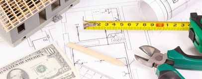 Electrical diagrams, work tools for engineer jobs, small toy house and currencies dollar, concept of building home cost. Electrical construction drawings or royalty free stock image