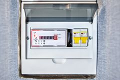 Electrical distribution board with electric meter. Household  electrical distribution box has 8 ways mounted of circuit breaker and tranparent plastic cap. In stock photography