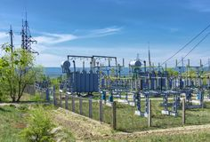 Electrical distribution transformer substation, against the background of green vegetation. The sky covered with clouds stock photo