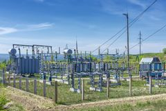 Electrical distribution transformer substation, against the background of green vegetation. The sky covered with clouds stock photography