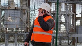Electrical Engineer with cell phone in the electric substation stock video footage