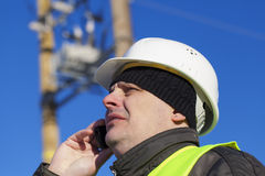 Electrical Engineer with cell phone. Near transformer Royalty Free Stock Photo