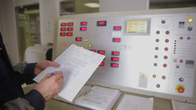 Electrical engineer checking parameters at a control panel of a nuclear plant, writing values into chart. Slider shot.