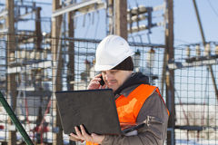 Electrical engineer with computer. Near the electricity substation Royalty Free Stock Image