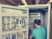 Electrical engineer configuring wires. Royalty Free Stock Photography