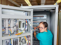 Electrical engineer configuring wires. Royalty Free Stock Photo