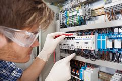 Electrical engineer examining fusebox with multimeter probe royalty free stock photos