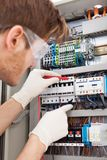 Electrical engineer examining fusebox with multimeter probe Stock Image