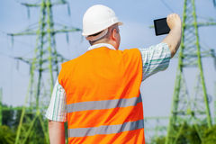 Electrical engineer filmed with tablet PC near high voltage power line Royalty Free Stock Image
